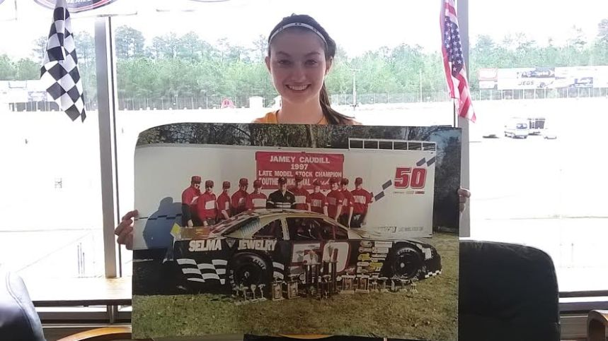 Haley  Moody displays a poster of Jamey Caudill's championship winning car and team, a car owned by her father Jerry Moody. (Southern National Motorsports Park photo)